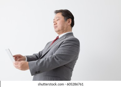 Businessman looking at mobile phone, middle aged man, presbyopia