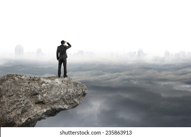 businessman looking on cliff with gray cloudy sky cityscape background