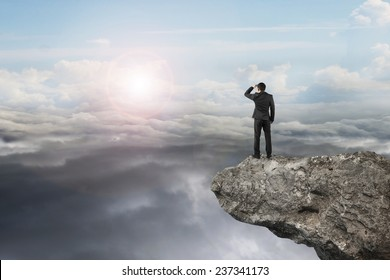 businessman looking on cliff with natural sky daylight cloudscape background