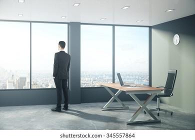 Businessman is looking out the window in modern loft style office 3D Render