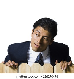 Businessman looking over wooden fence