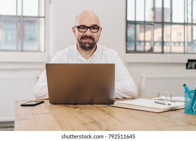 Businessman looking pensively at the camera as he sits at an office table working on a laptop computer in front of bright windows