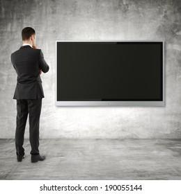 businessman looking  to plasma panel on wall