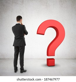 businessman looking at red question mark symbol