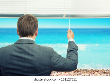 Businessman looking at sea out of the window