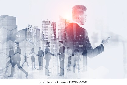 Businessman looking at smartphone screen with his colleagues walking and communicating in modern city with double exposure of hexagonal pattern. Toned image