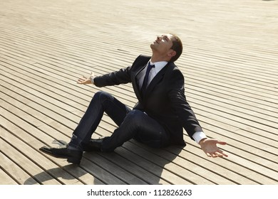 businessman looking up for something. young man sitting on wooden floor with open arms