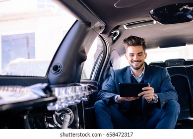 Businessman is looking at tablet and smiling in limousine