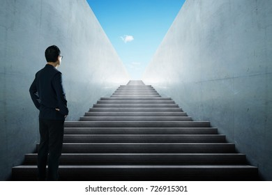 Businessman looking and thinking front of a stair infinty view .