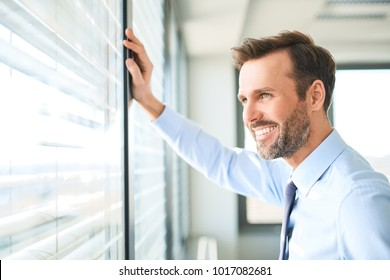 Businessman looking though the window at modern office
