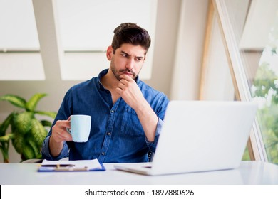 Businessman looking thoughtfully while drinking tea and working on laptop at home. Home office.