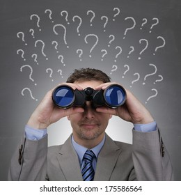 Businessman looking through binoculars searching for answers in front of question marks written on blackboard