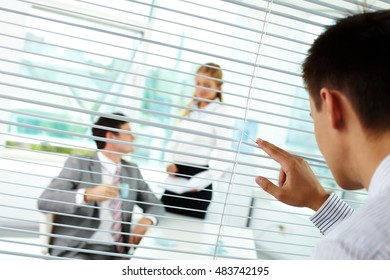 Businessman looking through blinds at his colleagues