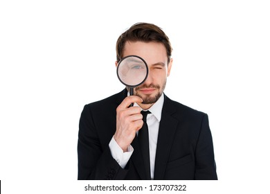Businessman looking through a magnifying glass directly at the camera with an enlarged eye in a conceptual image, isolated on a white background
