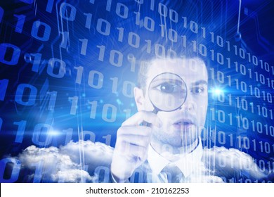 Businessman looking through magnifying glass against binary code on blue circuit board