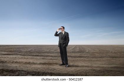Businessman looking through a pair of binoculars on a field