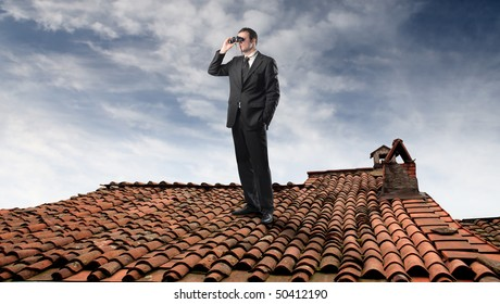 Businessman looking through a pair of binoculars on a rooftop
