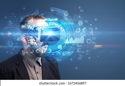 Businessman looking through Virtual Reality glasses with DEVELOPMENT inscription, innovative technology concept