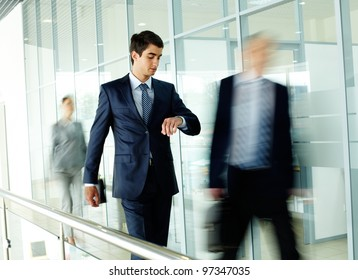 Businessman looking at watch with walking people on background