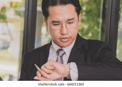 businessman is looking what time it is.