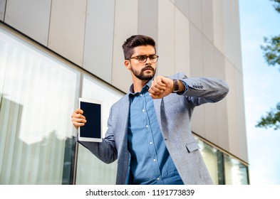 Businessman looking at wrist watch in front of office building