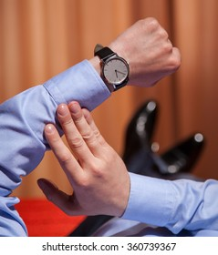 Businessman looking at the wristwatch and lying on the bed, closeup shot