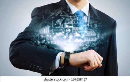 Businessman looking at wristwatch. Media technologies and innovations