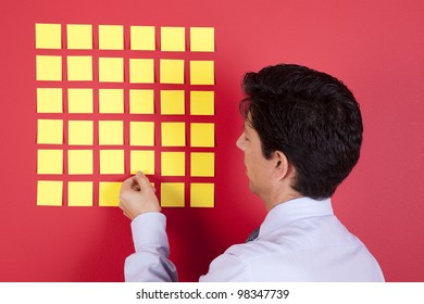 Businessman looking to yellow papers stick at a red wall