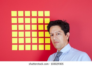 Businessman looking to yellow papers stickied at a red wall