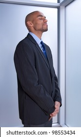 Businessman looking zen, standing with his eyes closed near a window.