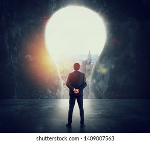 Businessman looks at a big hole on the wall shaped as a light bulb