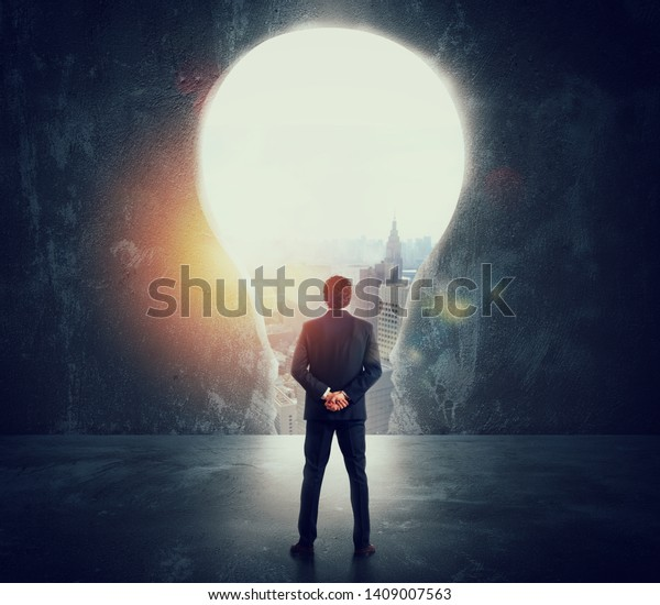 Businessman looks at a big hole on the wall shaped as a light bulb