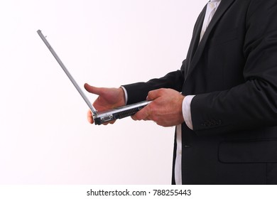 The businessman looks at the computer screen isolated on white background.