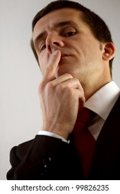 Businessman looks down while putting his finger on his lips
