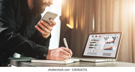 Businessman looks at laptop with charts,graphs, diagrams on monitor, making note in notebook while holding smartphone. Entrepreneur analyzes information, compares data. Internet marketing, e-learning.