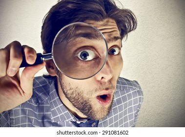 Businessman looks thru a magnifying lens