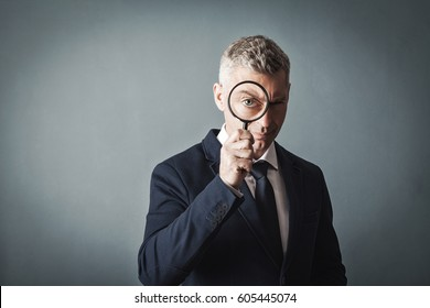 businessman looks at us through a magnifying glass on gray wall background.