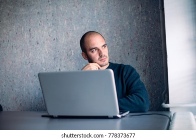 Businessman lost in his thinking, sitting in office and looking away.