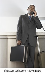 Businessman with luggage on telephone