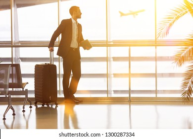 Businessman with luggage on travel at the airport in summer