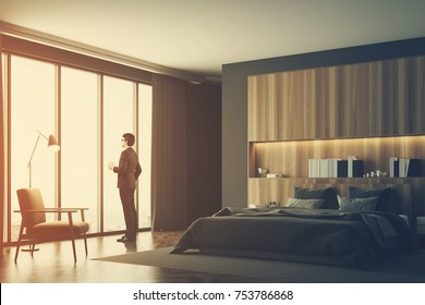 Businessman in a luxury bedroom interior with gray and wooden walls, a panoramic window, a master bed and an armchair. Side view. 3d rendering mock up toned image