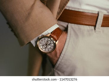 Businessman luxury style. Men style.closeup fashion image of luxury watch on wrist of man.body detail of a business man.Man's hand in a beige shirt with cufflinks in a pants pocket closeup. Toned