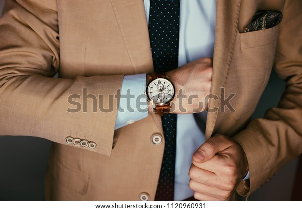 Businessman luxury style. Men style.Hand in pocket with wrist watch in a business suit close up.closeup fashion image of luxury watch on wrist of man.body detail of a business man in beige jacket.
