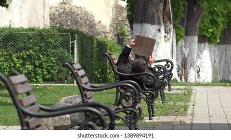 Businessman lying down on bench and read newspaper, spring alley , man rising u