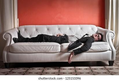 Businessman lying on a white sofa