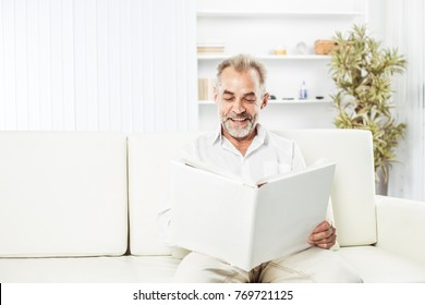 businessman with a magazine sitting on sofa in bright office.