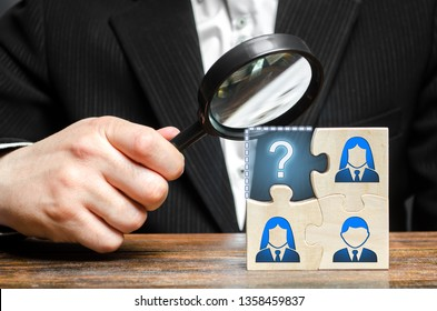 Businessman with a magnifying glass examines the missing part of the puzzle team. Search, recruitment staff, hiring leader. Creating an effective business team. Lack of specialists in the labor market