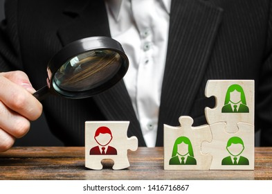 Businessman with a magnifying glass examines puzzle with an incompetent and toxic worker. The concept of the organization of the team and the business hierarchy. Management. appointment of the head