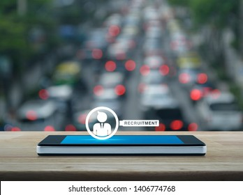 Businessman with magnifying glass icon on modern smart mobile phone screen on wooden table over blur of rush hour with cars and road in city, Business recruitment online concept