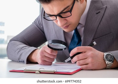 Businessman with magnifying glass studying agreement